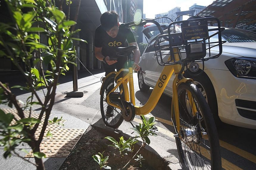 Mr Nicholas Chen, an operations team leader at ofo, unlocking one of the firm's bikes to move it to an approved bicycle-parking space. Doing a marshal's work often means travelling a distance of 50km to 60km a day, said Mr Chen.