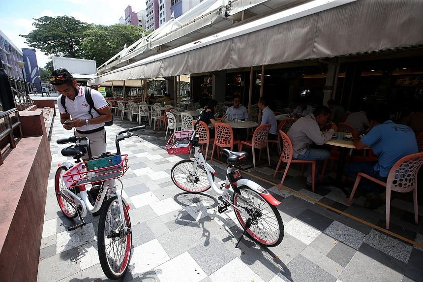 SG Bike operation supervisor Syed Al-Syahab, who found two of the firm's bikes parked illegally in the middle of a walkway, about to take them to an approved parking spot. In the six months at the firm, Mr Syed has also dealt with bikes with damaged