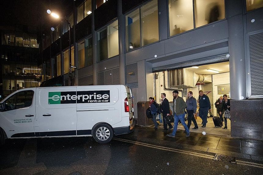 Officers from the Information Commissioner's Office leaving with a van believed to be carrying evidence after a search of the Cambridge Analytica headquarters in London on Friday.