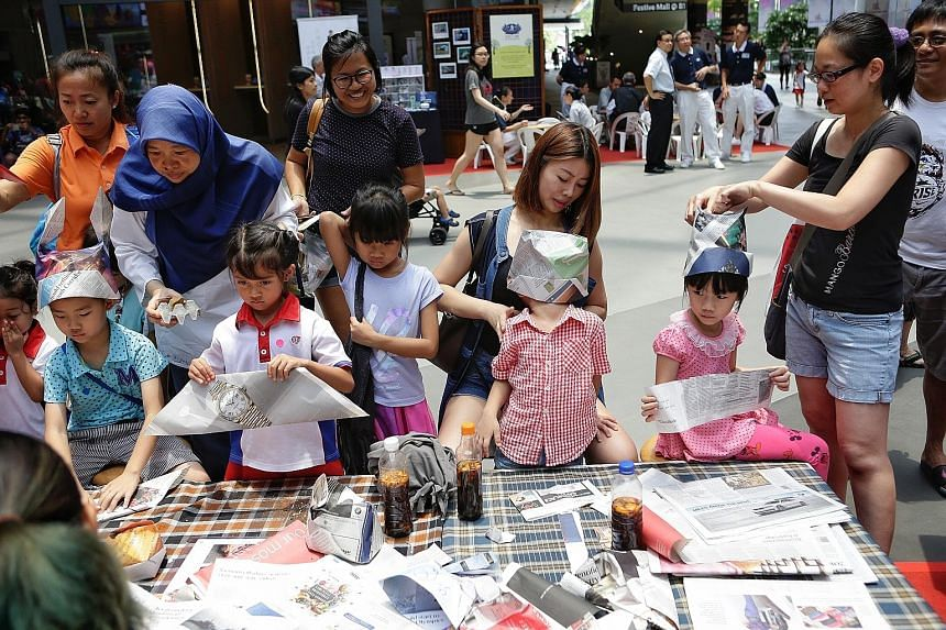 Children learning how to make hats out of newspapers at the Just-One-Earth Day carnival at Our Tampines Hub yesterday. The carnival offered children and their parents hands-on activities to engage them on environmental issues.