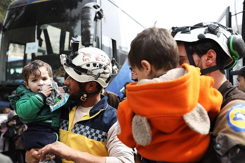 Members of the Syrian Civil Defence (known as the White Helmets) holding children as Syrian civilians and rebel fighters arrived in the village of Qalat al-Madiq yesterday, after being evacuated from Harasta in eastern Ghouta.
