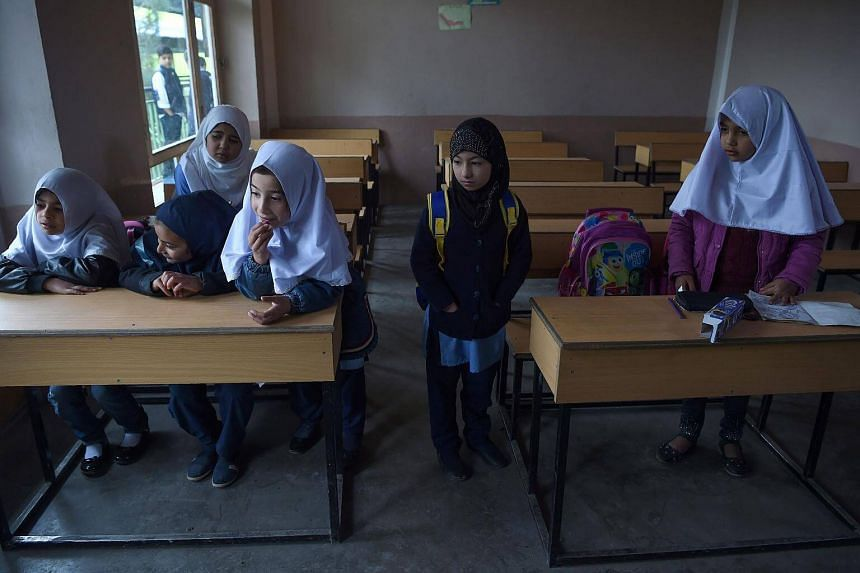 Dunya Saboori (second from right) attends class with other students on the first day of school for the year at a private school in Kabul on March 24, 2018.
