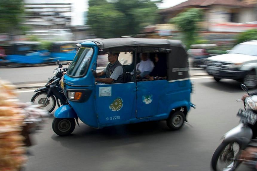 A three-wheeled bajaj taxi taking passengers to their destination in Jakarta.