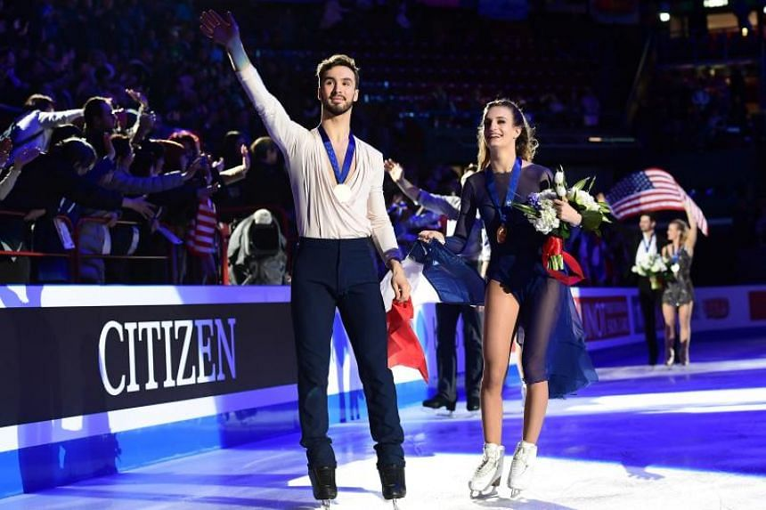 First-placed France gold medallists Gabriella Papadakis and Guillaume Cizeron celebrate and wave at the audience during the podium ceremony after competing in the Ice Dance-Free Dance program at the Milan World Figure Skating Championship 2018, in Mi