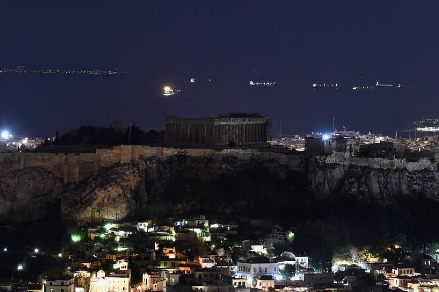 the ancient Temple of Parthenon atop Acropolis hill in the dark during the Earth Hour initiative in Athens on March 24, 2018.