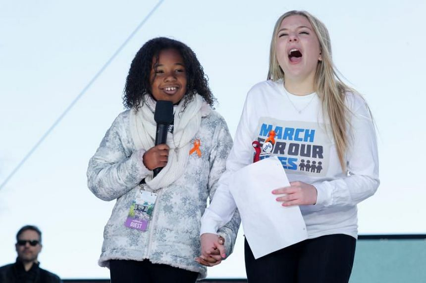 Martin Luther King Jr.'s 9-year-old granddaughter Yolanda Renee King holds hands with Marjory Stoneman Douglas High School student and shooting survivor Jaclyn Corin (right) as they address the March for Our Lives event at a rally in Washington, on M