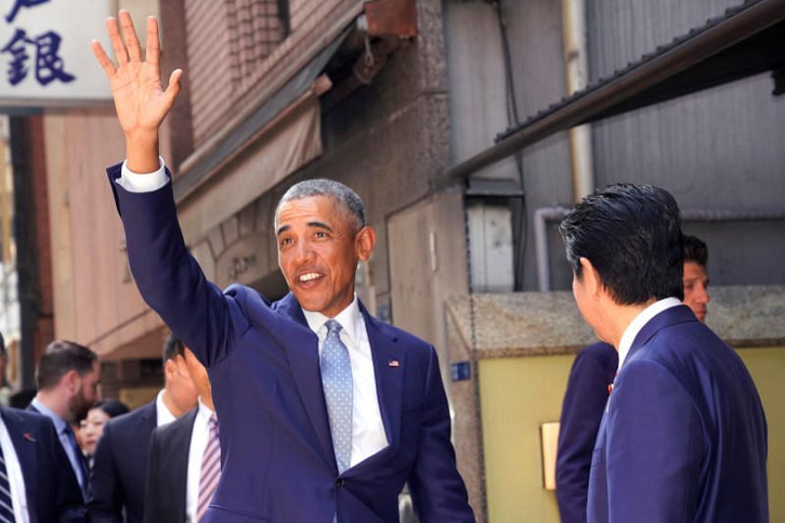 """Former US president Barack Obama waving to the media with Japanese Prime Minister Shinzo Abe in Tokyo, on March 25, 2018. Mr Obama said in a speech that North Korea was a """"real threat""""."""