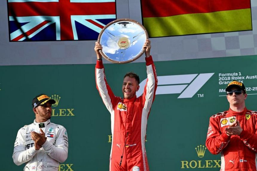 Ferrari driver Sebastian Vettel (centre) celebrating on the podium while flanked by second-placed Lewis Hamilton (left) and third-placed Kimi Raikkonen, on March 25, 2018.
