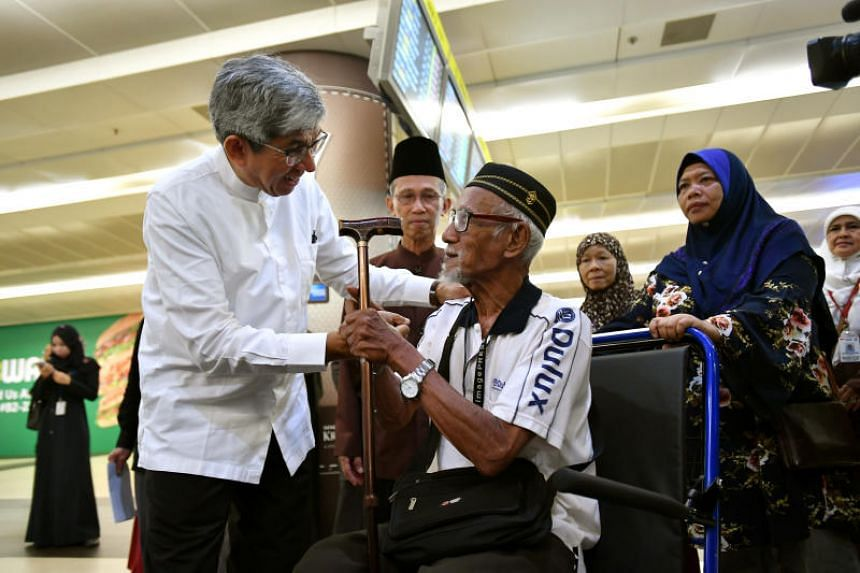 Minister-in-charge of Muslim Affairs Yaacob Ibrahim speaking to a friend of one of the pilgrims who went to Mecca, at Changi Airport, on March 25, 2018.