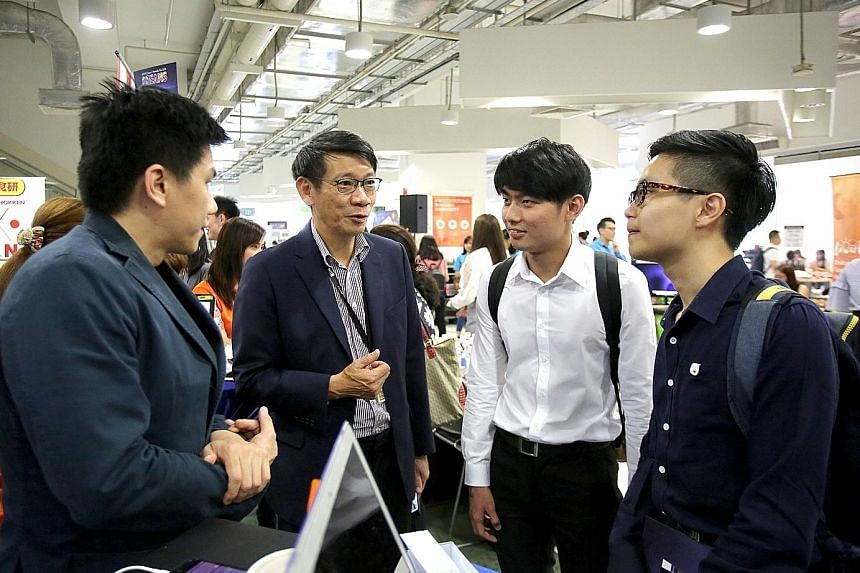 (From left) SIM alumnus Jasper Ong and SIM Holdings chief executive officer Lee Kwok Cheong with SIM students Tan Wei Liang, 24, and Jeremiah Toh Song Tat, 23, at the school's career fair last month that saw a record 126 companies taking part, includ