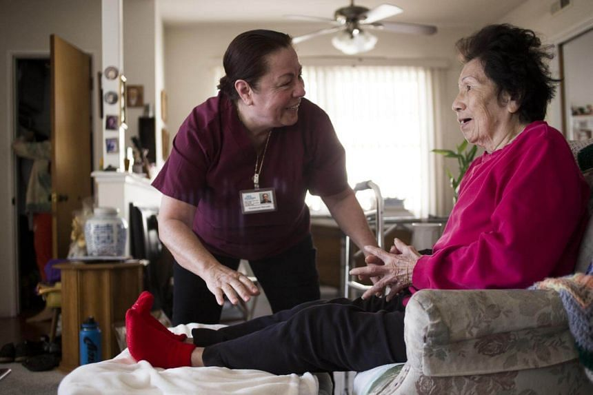 Caregiver Guadalupe Mercado, a Mexican immigrant and US citizen who works for 24Hr HomeCare, helps Olive Tanaka, 92, get settled in a chair at her home in Gardena, California on Feb 12, 2018.