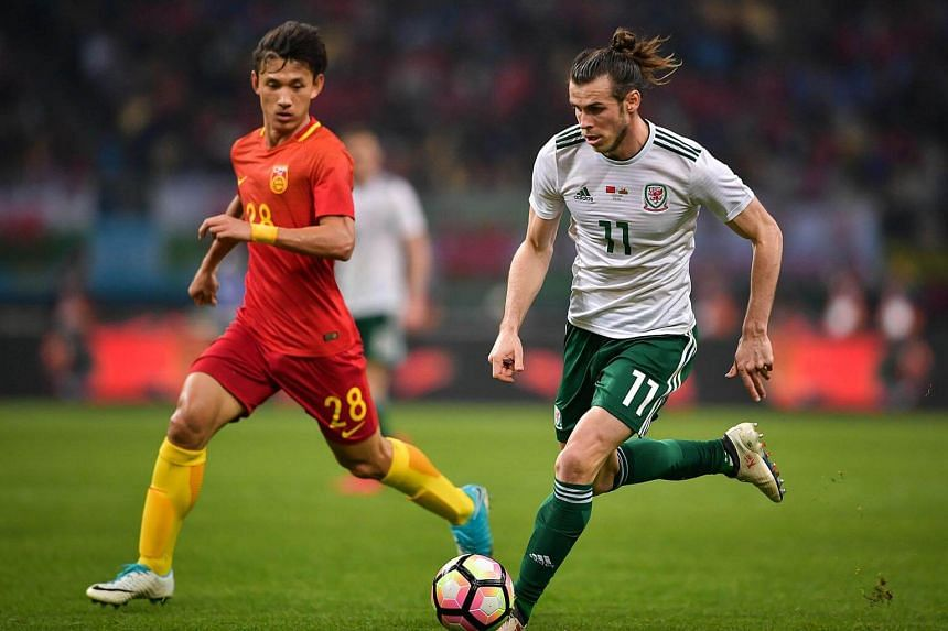 Wang Shenchao (left) of China fights the ball with Gareth Bale of Wales during their China Cup International Football Championship Semi-final match in Nanning, China, on March 22, 2018.
