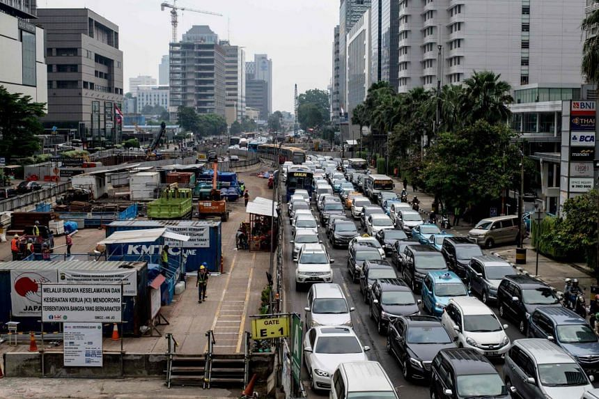 Motorists on the road next to a mass rapid transit construction site in Jakarta on March 6, 2018.