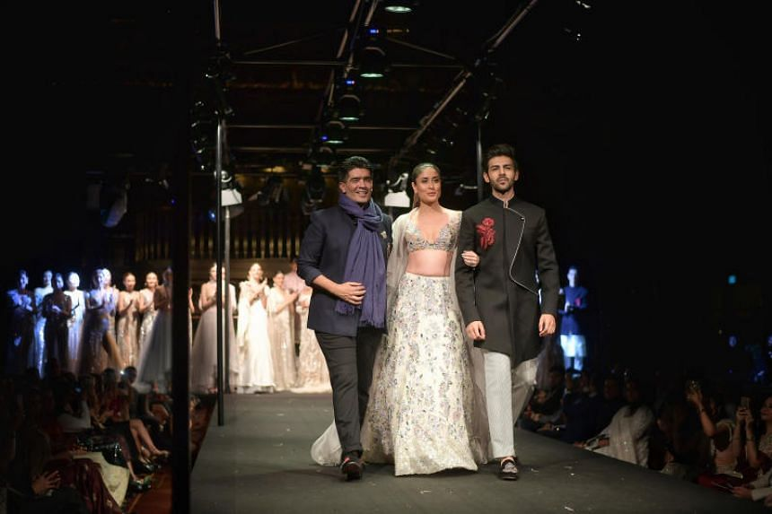 Indian designer Manish Malhotra joins Bollywood actress Kareena Kapoor and up-and-coming actor Kartik Aaryan on the runway at his Summer Couture 2018 show held at Atlas on March 25, 2018.