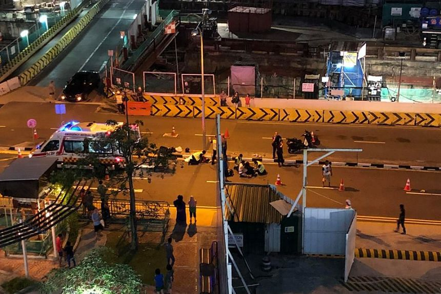 Foreign workers directing traffic after an accident occurred involving a car and a motorcycle in Ang Mo Kio Avenue 4, towards Yio Chu Kang Road on March 24, 2018.