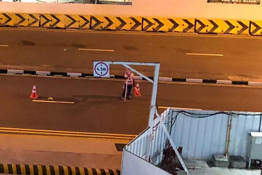 A foreign worker directing traffic after an accident occurred involving a car and a motorcycle in Ang Mo Kio Avenue 4, towards Yio Chu Kang Road on March 24, 2018.PHOTO: FACEBOOK/JUSTINA TYN