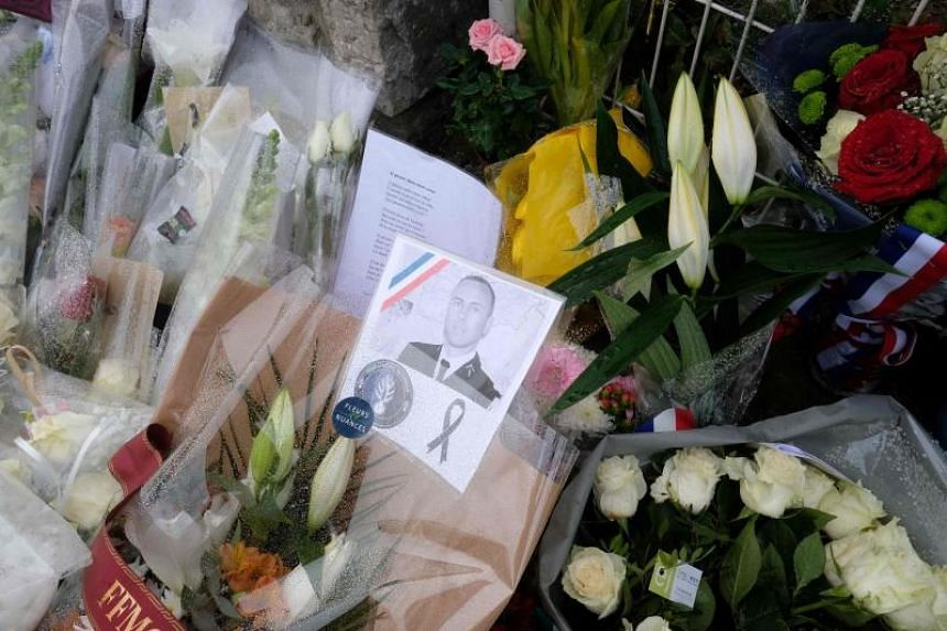 Flowers are laid outside the gates of the gendarmerie of Carcassonne where Lieutenant-Colonel Arnaud Beltrame worked in southwest France, on March 25, 2018, two days after he was killed in an attack.