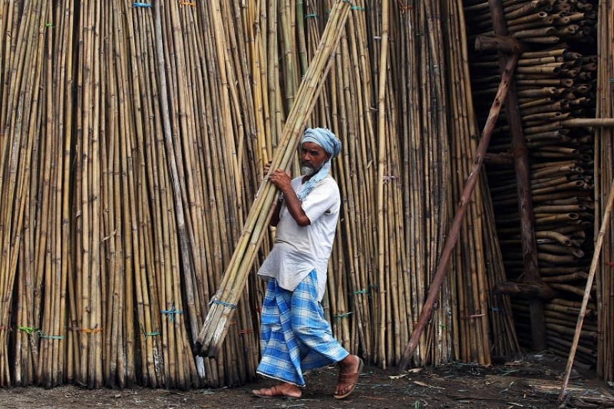 A man stacks bamboo sticks inside a godown in Mumbai, on Aug 10, 2017.