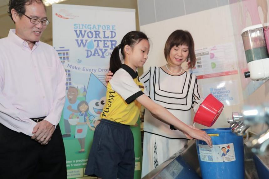 Dr Amy Khor helping Kuo Chuan Presbyterian Primary School pupil Isabelle Yap wash her hand using water from a pail.