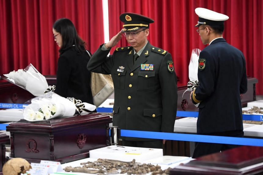 A Chinese military officer salutes near the remains of Chinese soldiers, who fought during the Korean War, during ceremonial rites to place the remains at a temporary military ossuary in Incheon, on March 26, 2018.