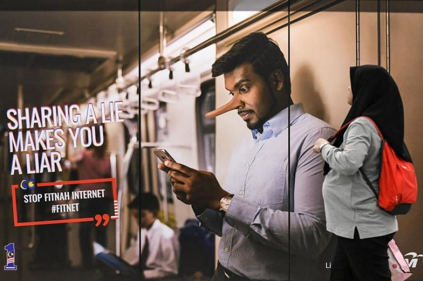 """A commuter walks past an advertisement reading """"sharing a lie makes u a liar"""" at a train station in Kuala Lumpur on March 26, 2018."""