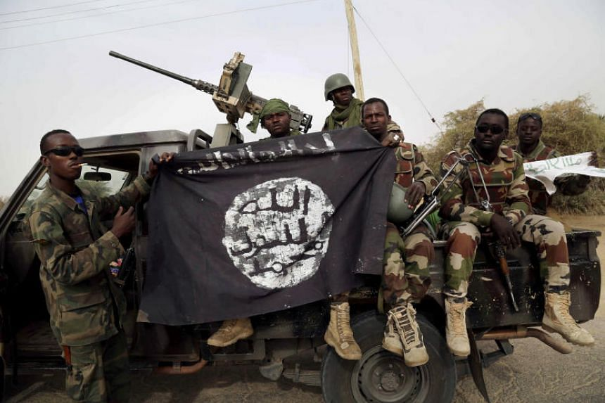 Nigerian soldiers hold up a Boko Haram flag. The attack killed five and wounded several people in a marketplace in south-east Niger.