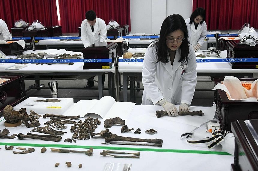 Members of South Korea's Agency for Killed In Action Recovery and Identification preparing to place the remains of Chinese soldiers, who fought during the Korean War, into coffins during ceremonial rites at a temporary military ossuary in Incheon, we