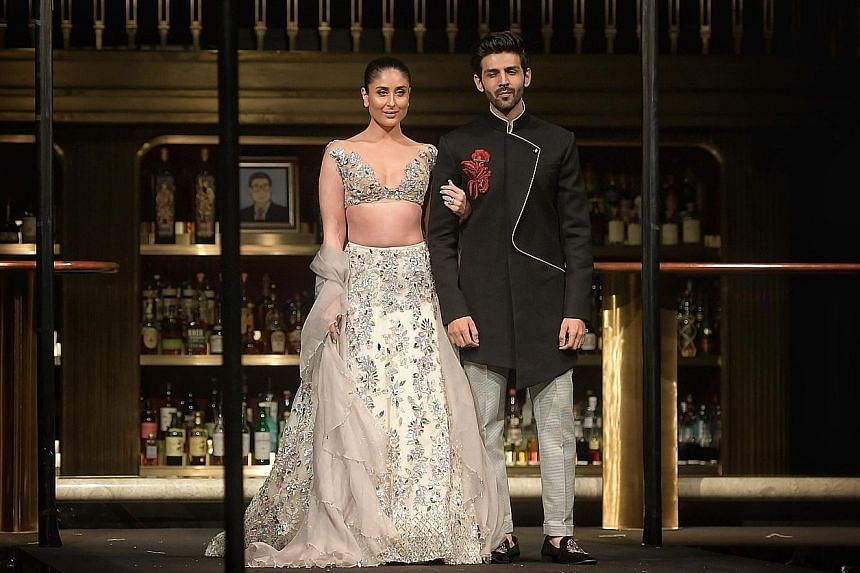 Indian designer Manish Malhotra's first full-fledged fashion show in Singapore features bridal wear modelled by a cast of about 30, including Bollywood celebrities Kareena Kapoor and Kartik Aaryan .