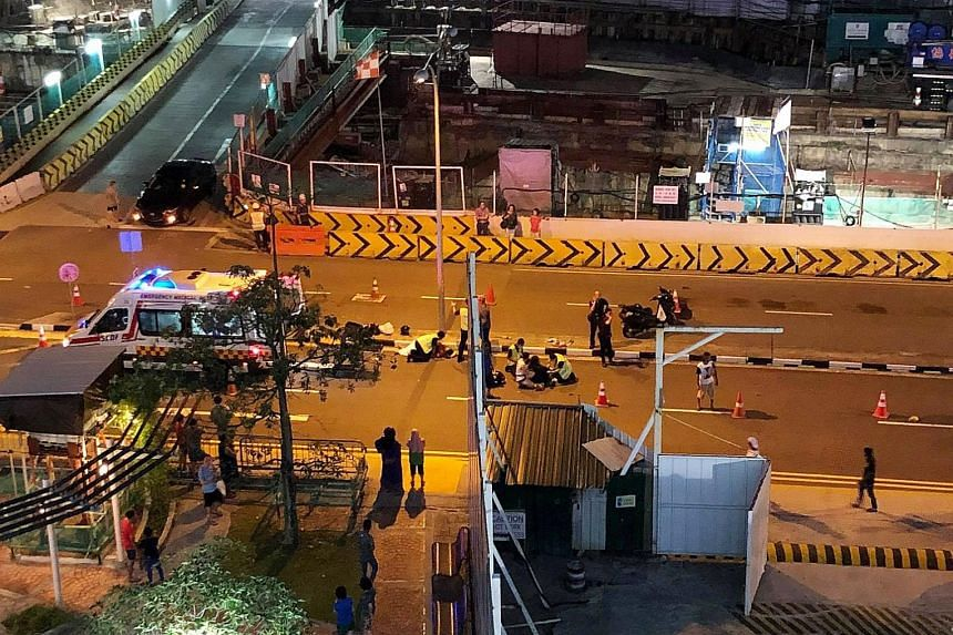 Foreign construction workers directing traffic after an accident involving a car and a motorcycle in Ang Mo Kio Avenue 4 last Saturday night.