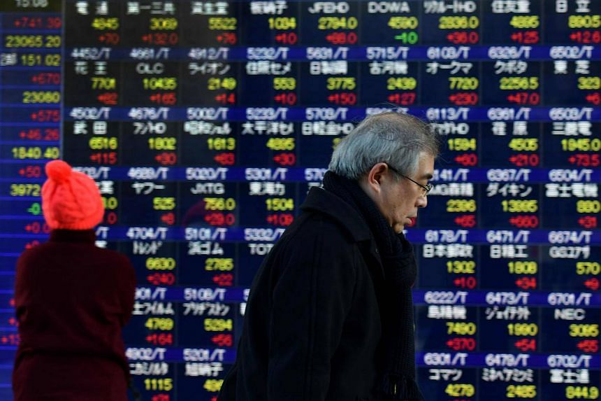 Pedestrians walk past an electronics stock indicator displaying share prices of the Tokyo Stock Exchange on Jan 4, 2018.