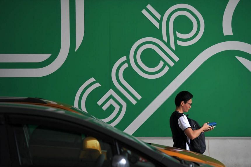 A passerby walking past a Grab logo at their main office in Midview City on June 23, 2017.