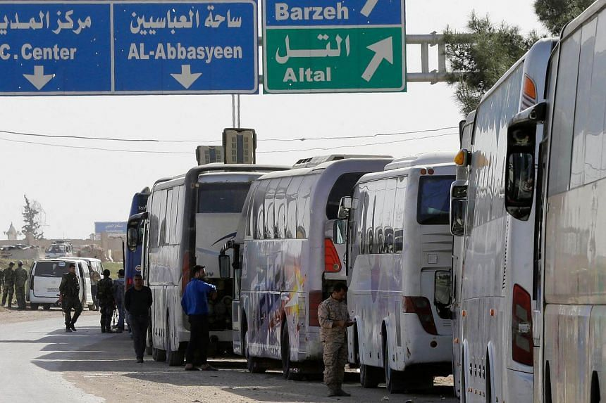 A convoy transporting Syrian civilians and rebel fighters evacuated from Eastern Ghouta arrives in a government-held area at the entrance of Harasta on the outskirts of Damascus.