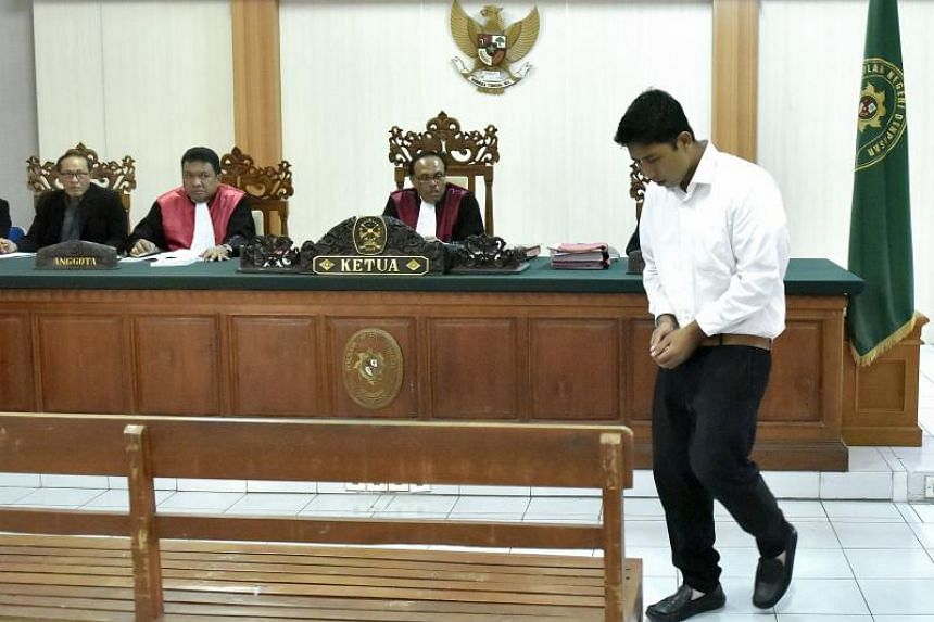 Indonesian defendant I Putu Astawa, 25, walks into a court in Denpasar on March 26, 2018, before being sentenced to 15 years in jail for stabbing an elderly Japanese couple to death during a botched burglary.
