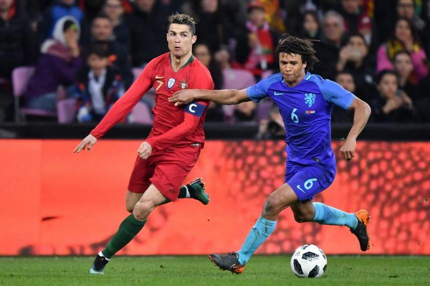 Portugal's forward Cristiano Ronaldo (left) fights for the ball with the Netherlands' defender Nathan Ake during the international friendly football match between Portugal and Netherlands at Stade de Geneve stadium in Geneva on March 26, 2018.