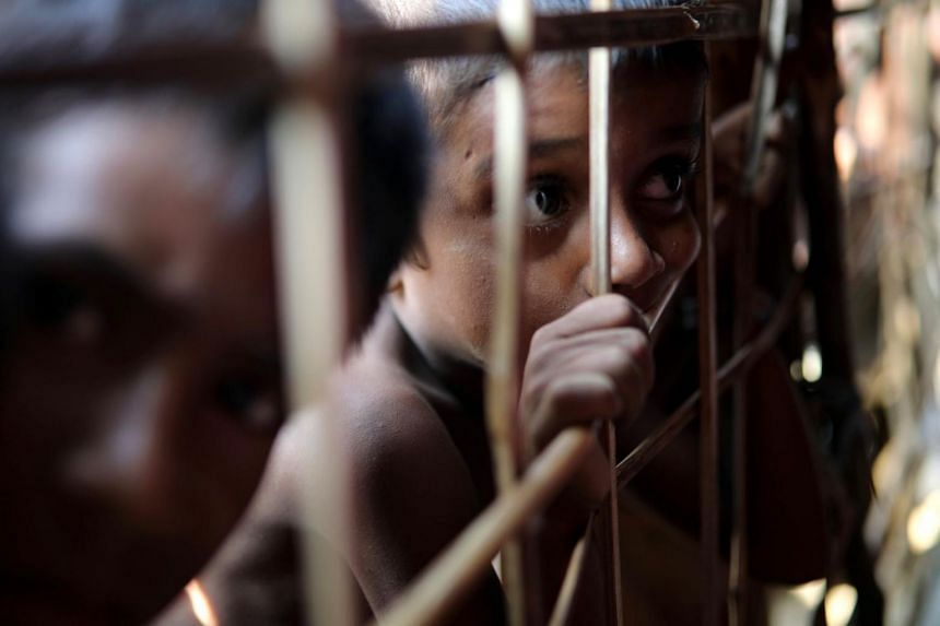 A Rohingya refugee looks through the fence at a refugee camp in Cox's Bazar, Bangladesh, on March 22, 2018.