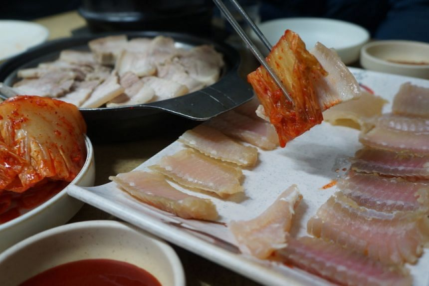 Hongeo (seen on the right), or fermented skate, is commonly eaten with kimchi and steamed pork belly.