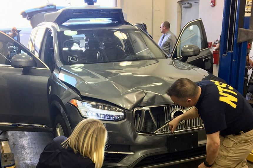 US National Transportation Safety Board (NTSB) investigators examining the self-driving Uber vehicle involved in a fatal accident in Tempe, Arizona, on March 20, 2018.