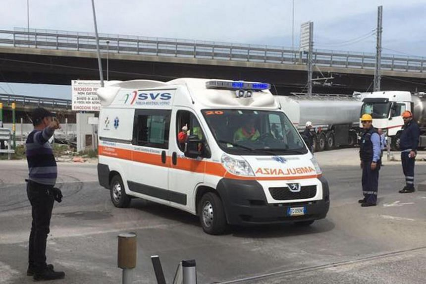An ambulance arrives at the site of the explosion of a fuel tank at the industrial port in Livorno, Italy.