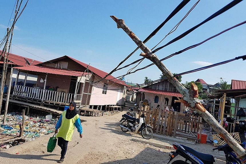 The village is poverty-striken and neglected. Electricity is wired to homes through overloaded power strips and tangled extension cords, and heaps of empty water bottles and food waste clog the coastline. Blue BN flags and red PPBM flags at the entra