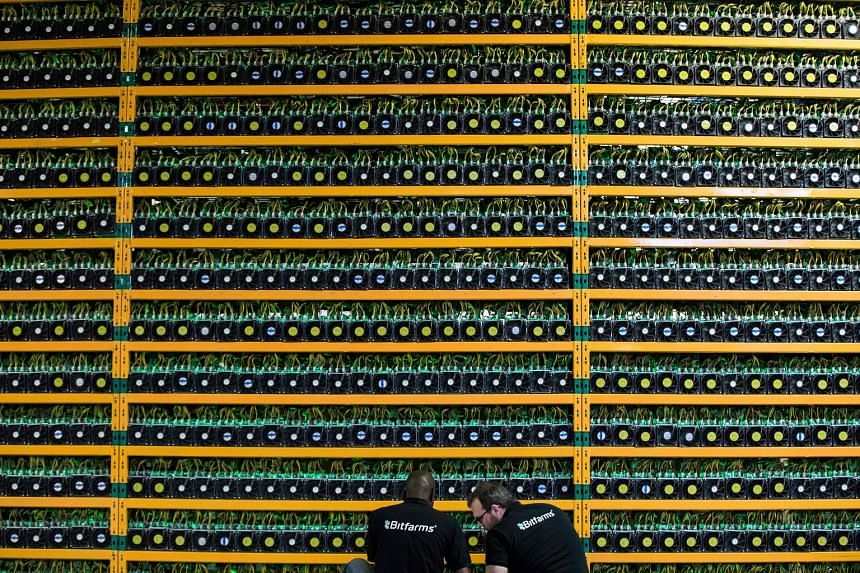 Technicians inspecting bitcoin mining at Bitfarms in Quebec, Canada. Bitcoin is independent of governments and banks and uses blockchain technology, where encrypted digital coins are created by supercomputers.