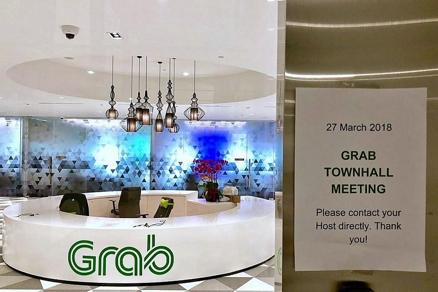 Left: A notice at Grab's office in Marina One West Tower about yesterday's townhall, which was attended by Grab co-founders Anthony Tan and Tan Hooi Ling, as well as Uber's Asia-Pacific chief business officer Brooks Entwistle. Below: Grab has said th