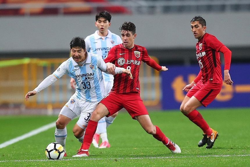Shanghai SIPG's Brazilian star Oscar (centre) being challenged by Ulsan Hyundai's Park Joo Ho during their AFC Champions League group stage match at home on March 7. The elite Asian club competition is part of the Asian Football Confederation's stabl