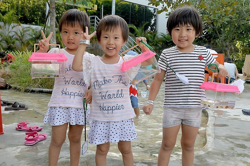 Far left: (From left) Zhang Mulai, Zhang Muqing and Chen Zhihan, all aged four, showing off their catch at Orto last Saturday. Left: Six-year-old Lynelle Lee fishing with her friends from Little Wonders Montessori Childcare at Fish @ Bugis+ last week
