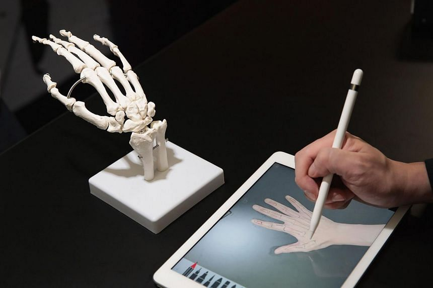 A guest draws the bones of a hand on Apple's new 9.7-inch iPad during an event held to introduce the device.