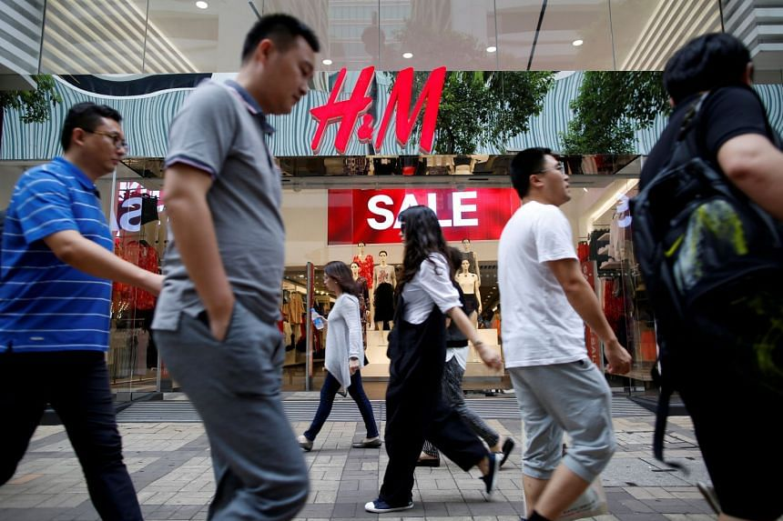 People walking past a H&M fashion chain store at the Tsim Sha Tsui shopping district in Hong Kong.