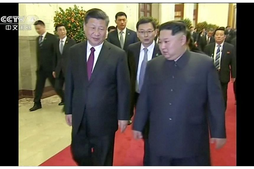 Chinese President Xi Jinping walks with North Korean leader Kim Jong Un, in this still image taken from a video released on March 28, 2018.