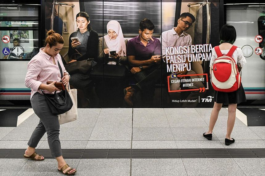 """An advertisement with text reading """"sharing a lie makes you a liar"""" at a train station in downtown Kuala Lumpur on March 26, 2018."""