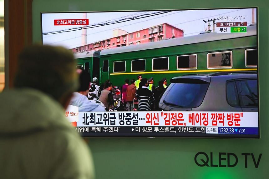 A man watches a TV news report about a suspected visit to China by North Korean leader Kim Jong Un.