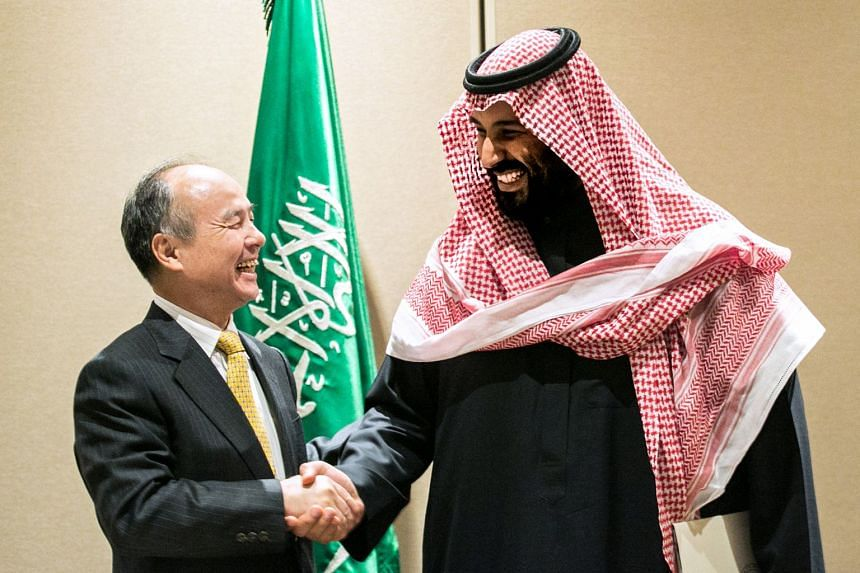 Masayoshi Son, chairman and chief executive officer of SoftBank Group Corp (left) shakes hands with Mohammed bin Salman, Saudi Arabia's crown prince, after signing an agreement in New York,  on March 27, 2018.