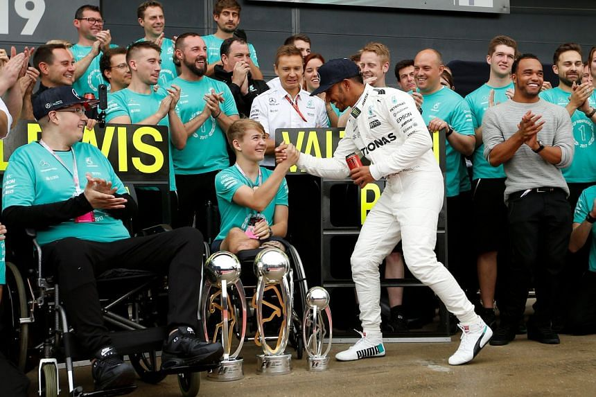 Mercedes' Lewis Hamilton celebrates his win with Billy Monger at the British Grand Prix 2017 in Silverstone, Britain on July 16, 2017.